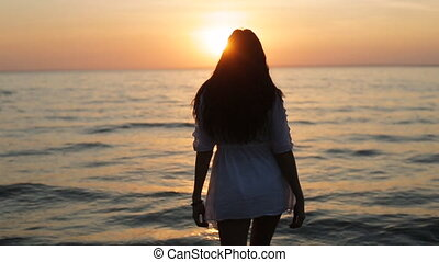 a girl walks into the sea at sunset slow motion