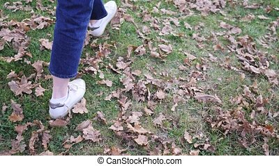 A girl walks on the lawn in jeans and sneakers, warm winter...