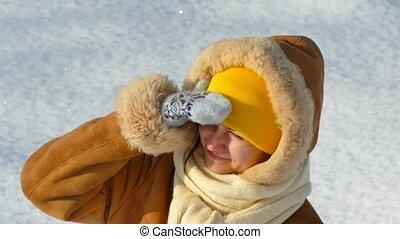 A girl walks through deep snow in winter. The sun on a winter day.