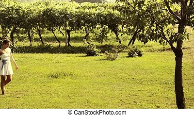 A girl walks through the vineyards
