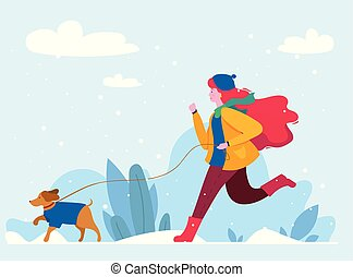 A girl walks with her dog in winter park.