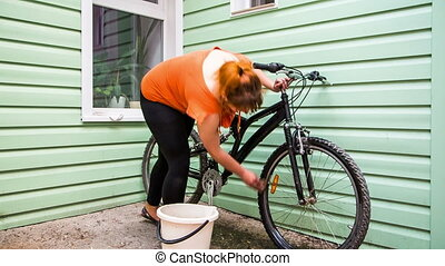 A girl washes a bicycle outside in a bucket