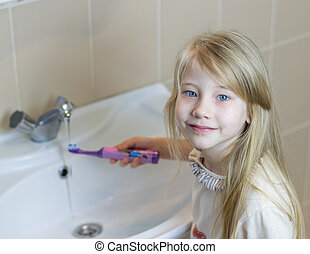A girl washes an electric toothbrush after brushing her teeth.