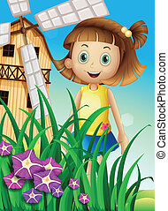 A girl watching the flowers in the garden near the windmill
