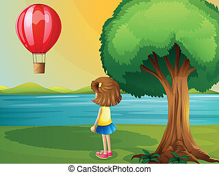 A girl watching the hot air balloon at the riverbank