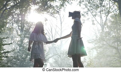A girl wearing VR goggles is holding hands with her friend and walking through the forest exploring virtual reality