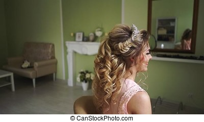 A girl with a beautiful hairstyle sits sideways to the camera and smiles.