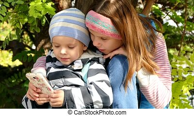 A girl with a boy is using a smartphone.