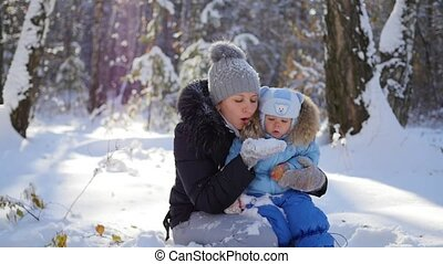 A girl with a child playing with snow in the park in a Sunny day