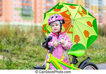 girl with a green umbrella stands with her Bicycle