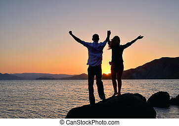 A girl with a guy raised his hands to the sun - A girl with...