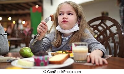 A little girl with a protective medical mask on her chin eats a sausage in the hotel dining room. travelling and resting during a pandemic.