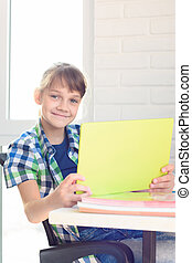 A girl with a tablet sits at a table at home and joyfully looked into the frame