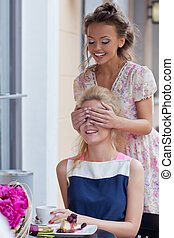 a girl with a toothy smile in summer dress is covering eyes of her beautiful friend who is eating pie with berries