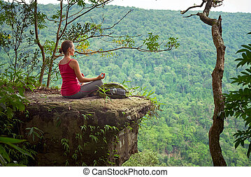 A girl with backpack sitting on the cliff and relaxing high in mountains on the background of sunrise