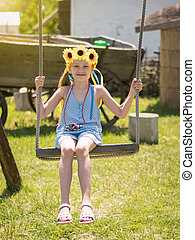 A girl with bright yellow flowers on his head swinging on an old swing in the village.