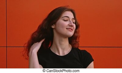 A girl with brown hair poses against a wall shaking her hair...