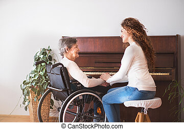 A girl with grandmother in wheelchair by the piano.