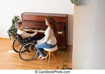 A girl with grandmother in wheelchair playing the piano.