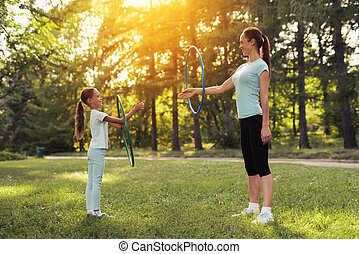 A girl with her mom practicing with gymnastic hoops in the park