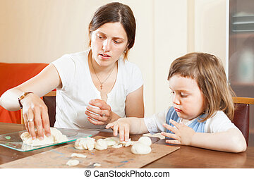 A girl with her mother learns to mold dough figurines
