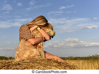 A girl with long blonde hair hugging a shaggy dog on a bright sky background nature