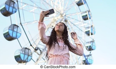 a girl with long hair does selfie using a phone while standing near the Ferris wheel. slow motion