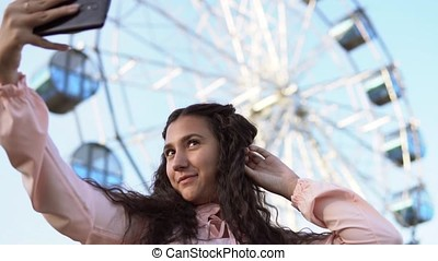 a girl with long hair does selfie using a phone while standing near the Ferris wheel. slow motion. Portrait