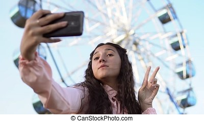 a girl with long hair in a dress makes selfie using a phone standing near the Ferris wheel. slow motion. Portrait
