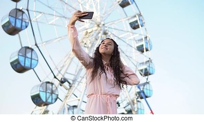 a girl with long hair in a dress makes selfie using a smartphone standing near the Ferris wheel. 4K