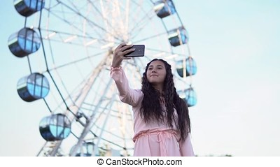 a girl with long hair in a dress makes selfie using a smartphone standing near the Ferris wheel. slow motion.