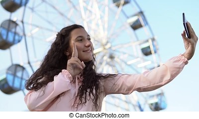 a girl with long hair in a pink dress makes selfie using a phone standing near the Ferris wheel. slow motion.