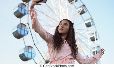 A girl with long hair in a pink dress makes selfie using a smartphone standing near the Ferris wheel. 4K