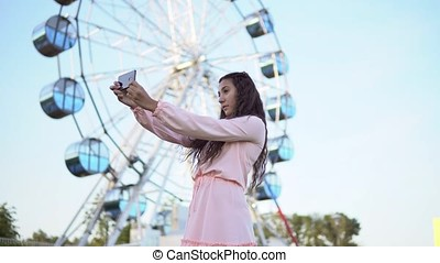 a girl with long hair in a pink long dress makes selfie using a smartphone while standing near the Ferris wheel. 4K