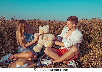 A girl with long hair receives teddy bear gift from her young boyfriend. Happy smiling rejoice. Sitting in a wheat field in summer. Romantic date, newlyweds, happy new family.