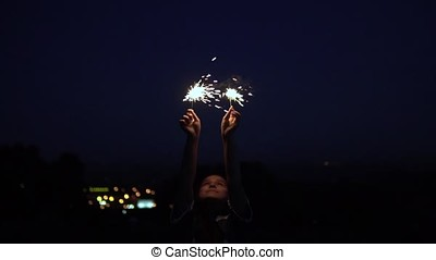 A girl with long hair stands against the background of the city at night and holds fireworks in her hands. slow motion.