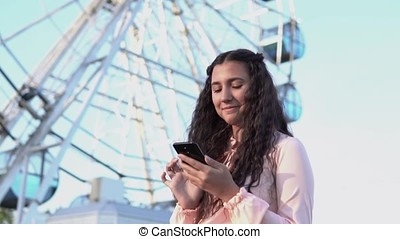 a girl with long hair uses a smartphone standing near the big Ferris wheel and an amusement park. slow motion