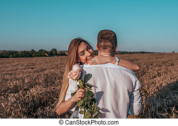 A girl with long hairs standing in wheat field is smiling happy. A man gives flowers behind his back. Concept of love and surprise gift, marriage proposal, engagement.