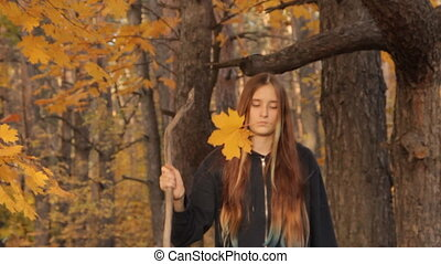 A girl with long loose hair and a stick in her hands, and a yellow maple leaf in her teeth stops, looks around thoughtfully.