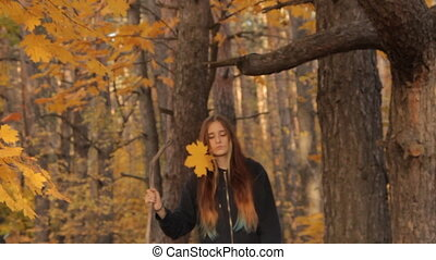 A girl with long loose hair and a stick in her hands, and a yellow maple leaf in her teeth coming out of the forest thoughtfully and passing by the camera.
