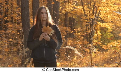 A girl with long loose hair standing on a cleaning in the middle of an autumnal yellow forest lit with the setting sun and holding a bunch of maple leaves in her hand. She moves out of the frame.
