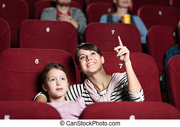 A girl with mother at the cinema
