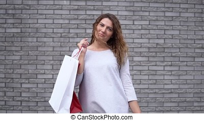 A girl with packages after shopping with a good mood against a wall of stones. slow motion. HD