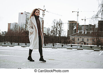 A girl with red curly hair in white coat. City construction in the background
