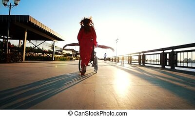 A Girl With Red Hair In An Orange Dress Rolls A Disabled Guy...
