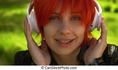 A girl with red hair listens to music - beautiful woman with...