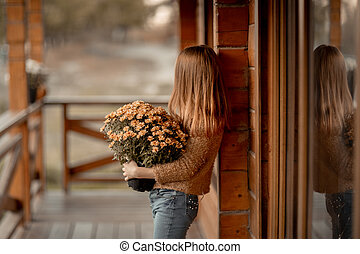 A girl with red hair stands near a wooden house and holds a bouquet of flowers in her hands