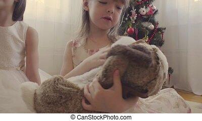 A girl with stuffed dog near christmas tree 4K
