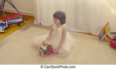 A girl with stuffed dog sitting on the floor in beautiful...