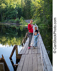 A girl with two children are standing on the old wooden bridge across a quiet river